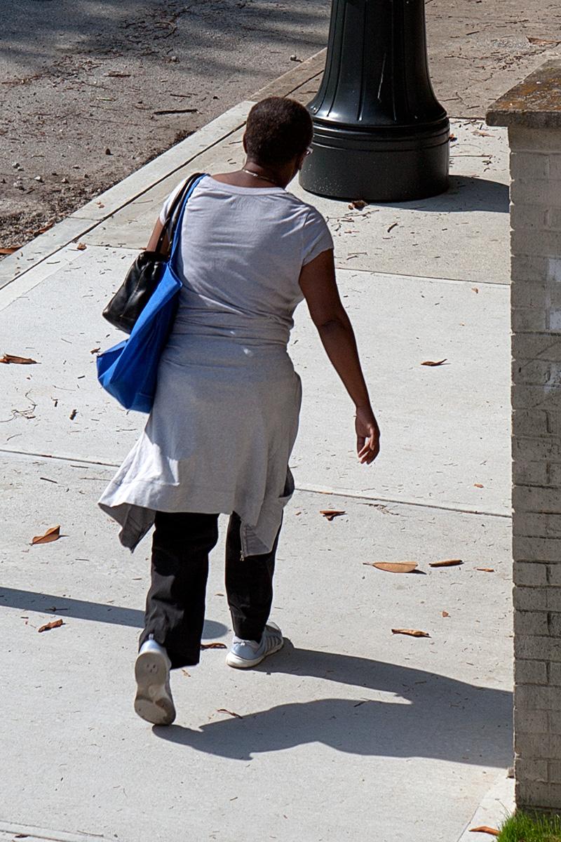 Frau von hinten auf dem Bürgersteig