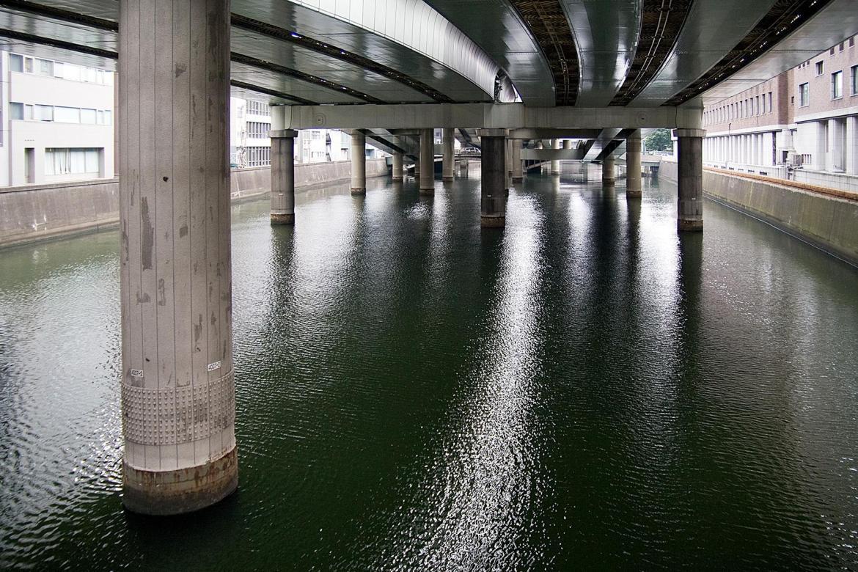 Autostraßenpfeiler im Fluss in Tokyo