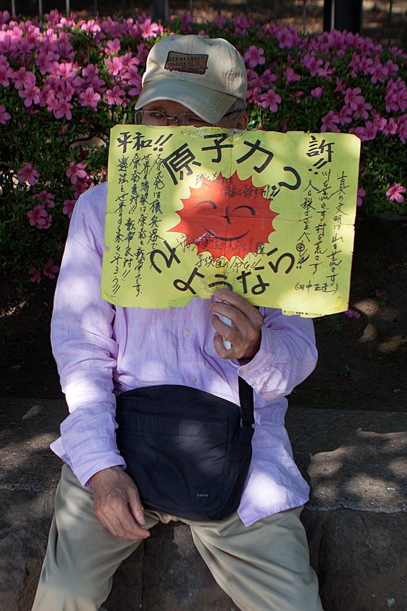 Ein älterer Mann zeigt ein Schild gegen AKWs auf der Seite Stadterkundung.com