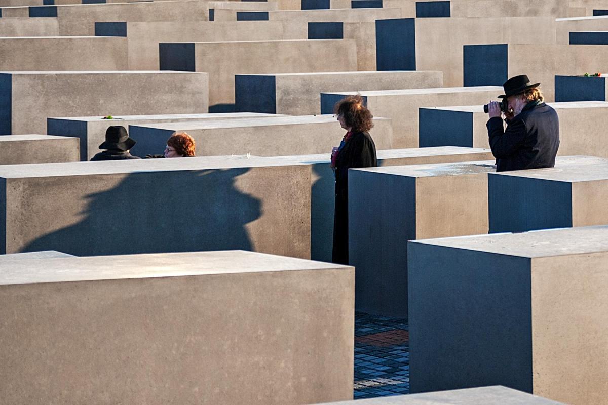 Menschen fotografieren sich bei den Steelen auf dem Holocaust Mahnmal in Berlin