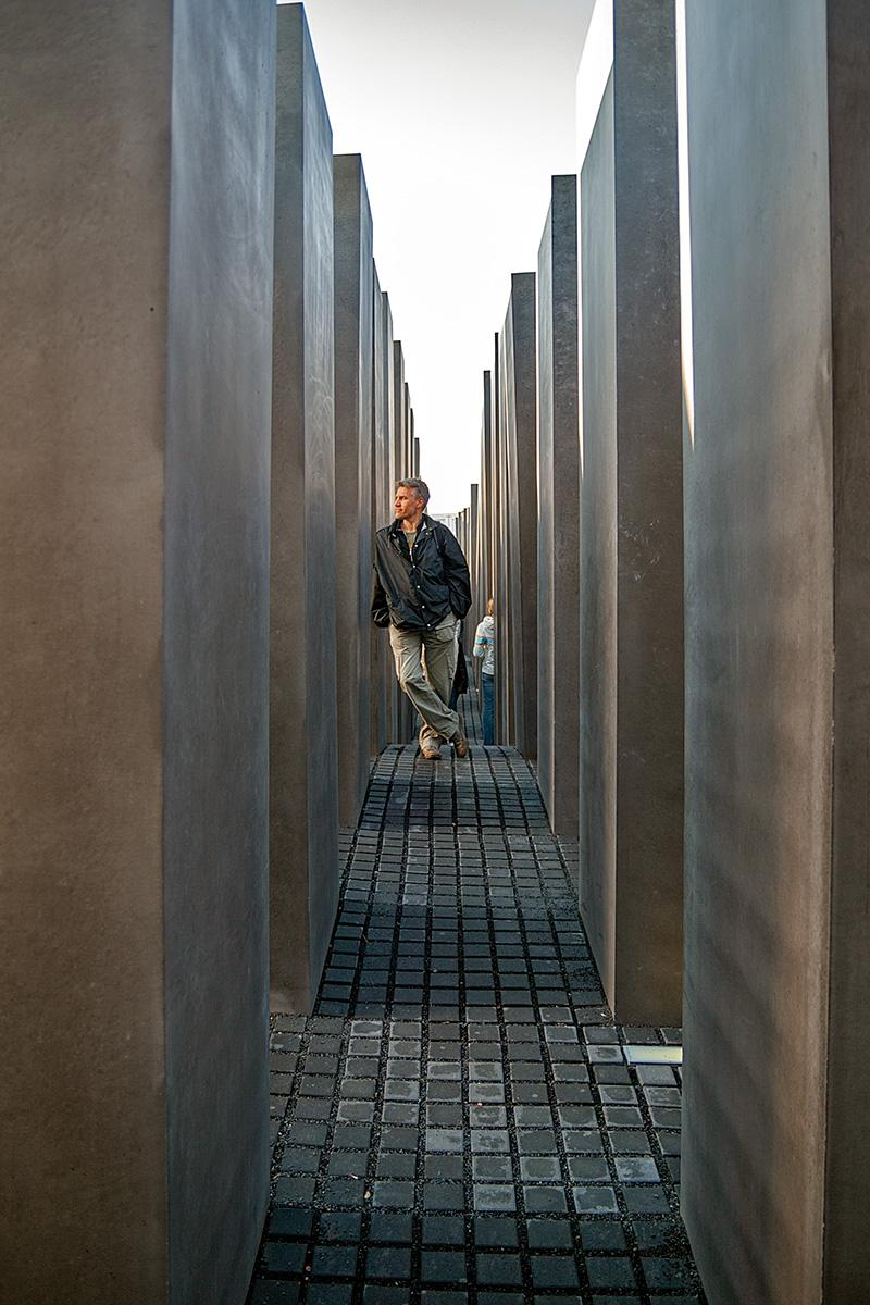 Mensch zwischen den Steelen auf dem Holocaust Mahnmal in Berlin