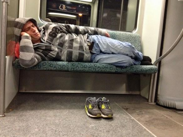 Mann schläft auf S-Bahn-Sitzen