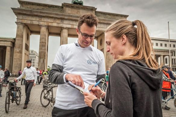 Mann, junge Frau mit Unterschriftenliste
