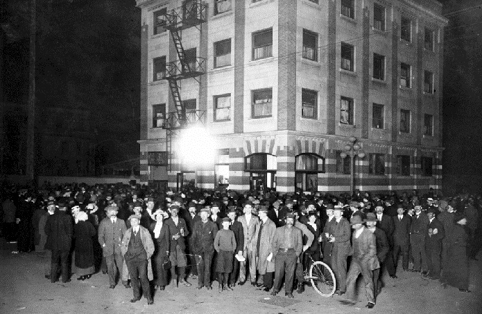 Spectators gather outside the Kaiserhof Hotel, southwest corner of Johnson and Blanshard Streets, Victoria, May 8, 1915. (BC Archives photo A-02709, detail)