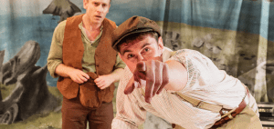 A male actor in a old-style cap points excitedly at the reader while a curious performer watches from behind.