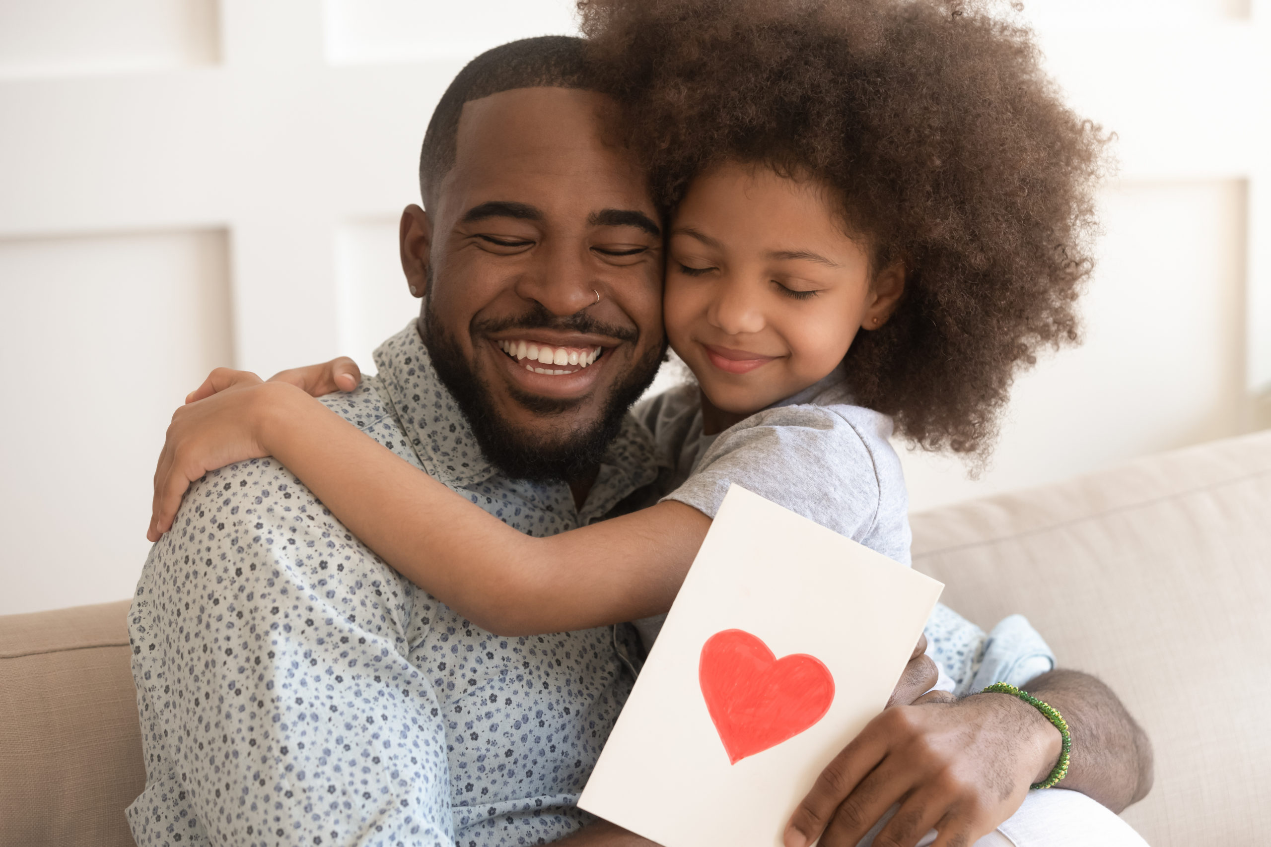 A black man hugging his black son while holding a card with a red heart painted on it