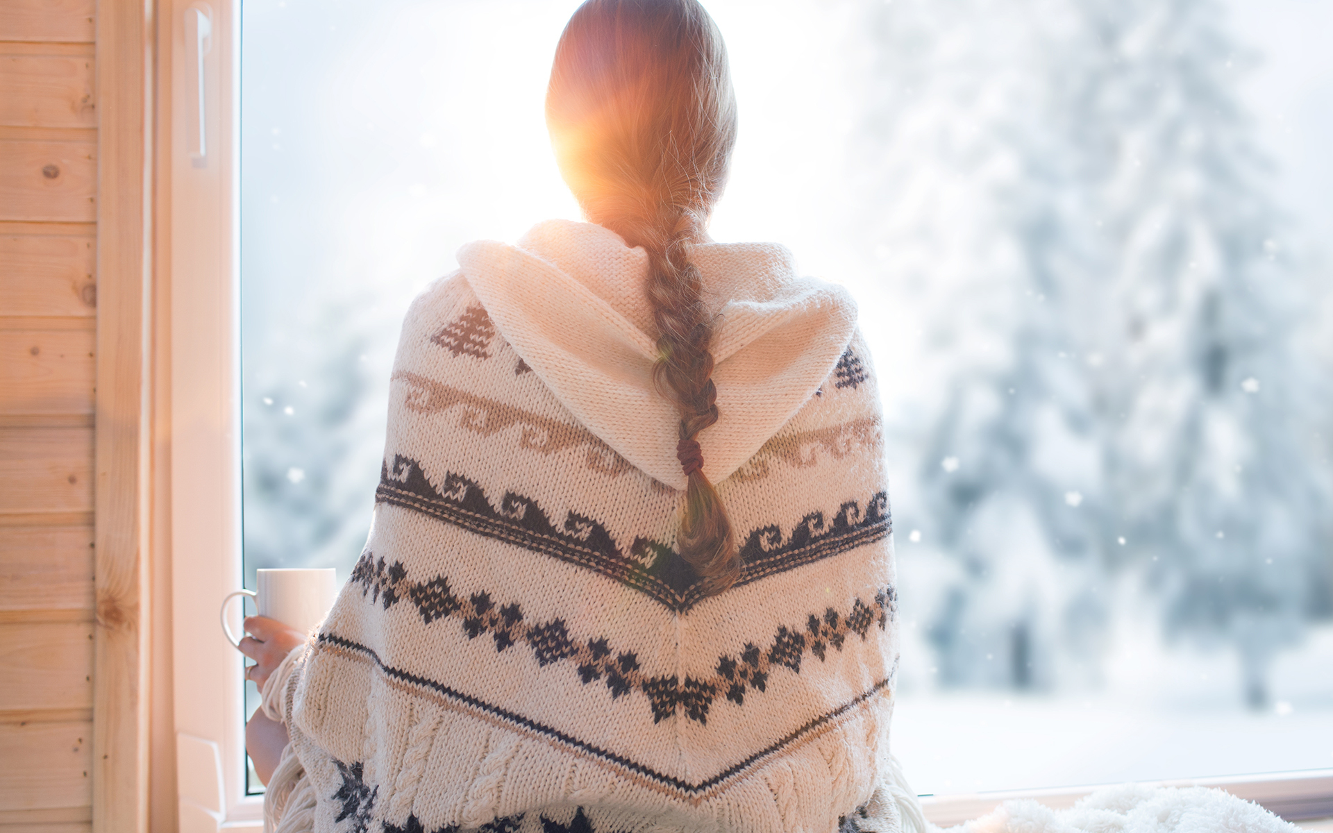 A Guided Practice For Managing Holiday Expectations - Woman wearing nordic style poncho sitting facing a window with cup of coffee, winter woods landscape outside