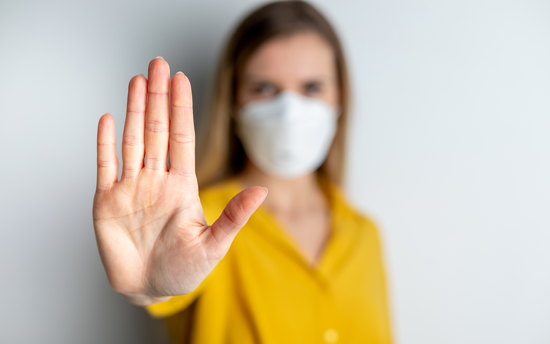 Woman wearing face protection in prevention of coronavirus showing gesture