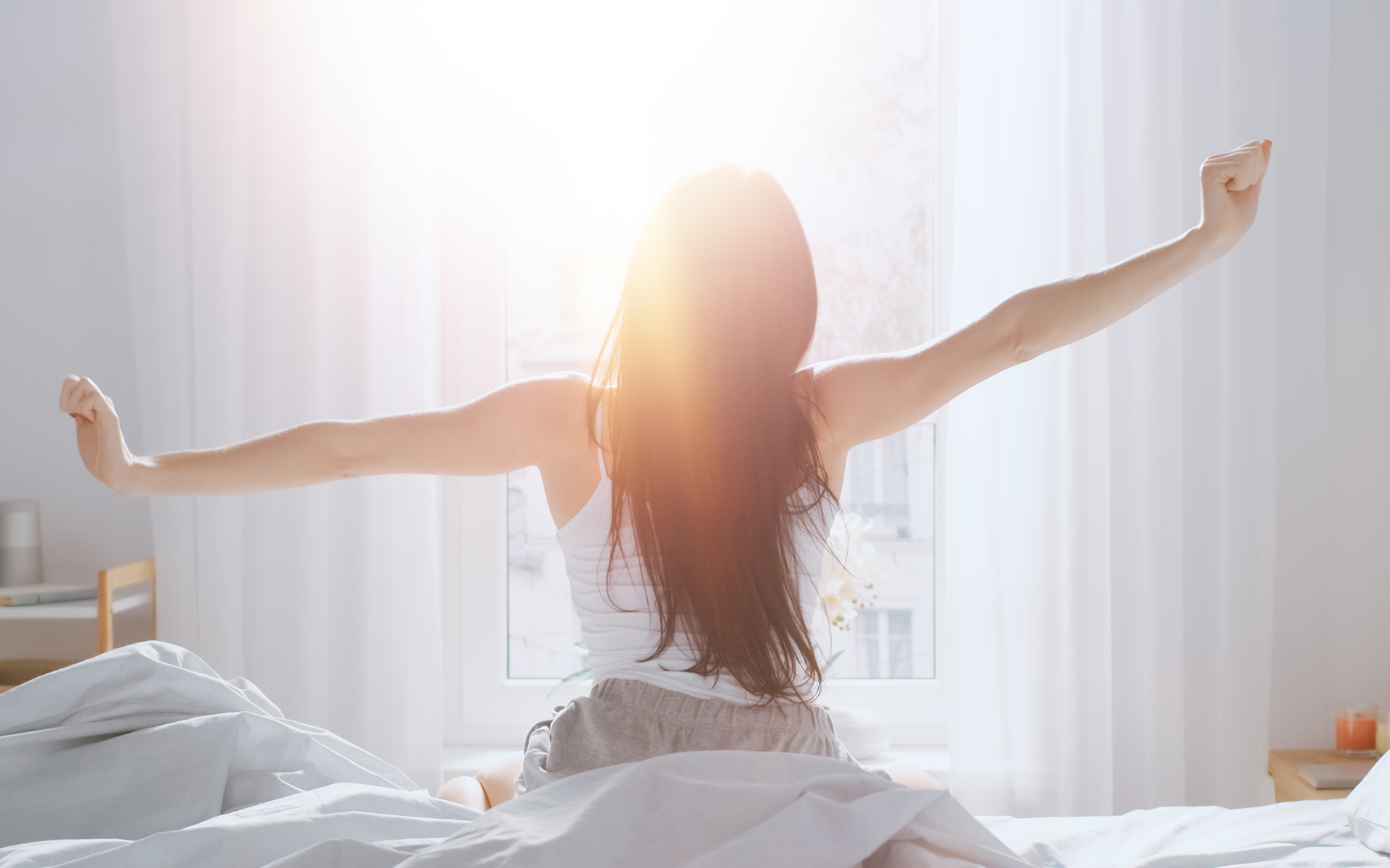 Woman waking up in the morning - how to create your own morning routine