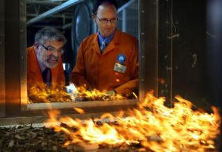 A photograph showing research scientists Jim Gould and Andrew Sullivan, keeping a watchful eye as fire spreads in the Pyrotron.