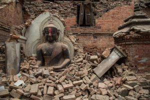 A photograph showing the aftermath of the Nepal earthquake: an intact statue of Buddha among the rubble and destruction.