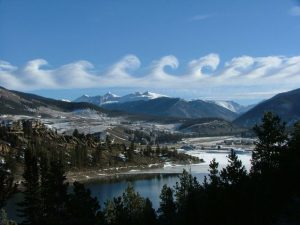 A photograph of curly Kelvin-Helmholtz clouds over some mountains.
