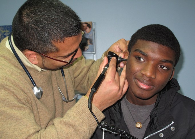 A student getting a check-up at school from Urban Health Plan's Dr. Viju Jacob.
