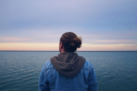 woman in blue denim jacket standing near body of water during daytime