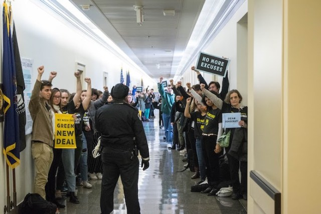 "Activists lined up on congressional halls during the November 2018 sit-in of Nancy Pelosi's office to demand a Green New Deal. A police officer is looking at people as they hold up their fists and signs saying ""No more excuses"" and ""We need a Green New Deal""."