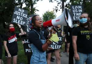 "A Sunrise activist speaks into a megaphone while fellow protesters stand behind holding signs saying ""No Justice No Sleep"" and ""Look Us In The Eyes""."