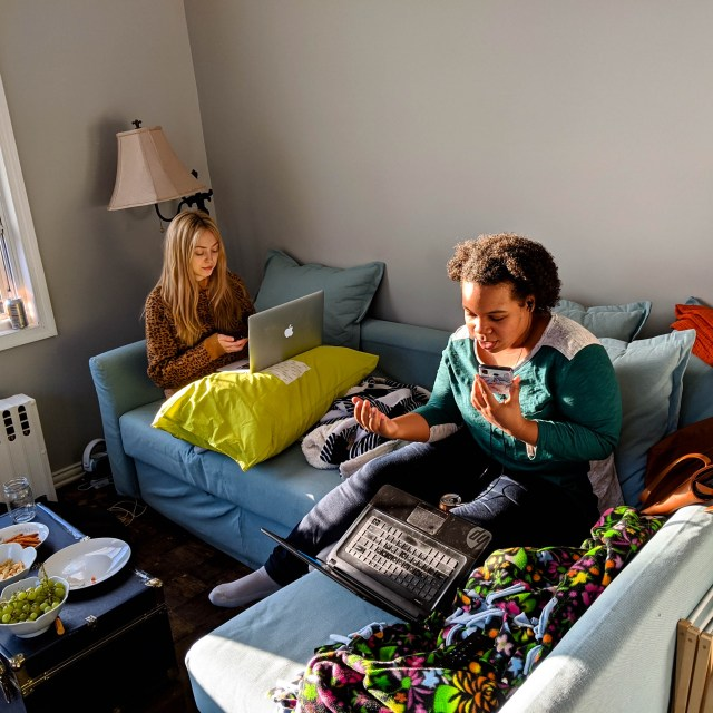 Two people phonebanking on their couch, calling voters to support Green New Deal champions.