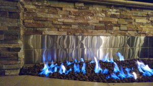 Stacked Stone Outdoor Fireplace with Stainless Steel Tile