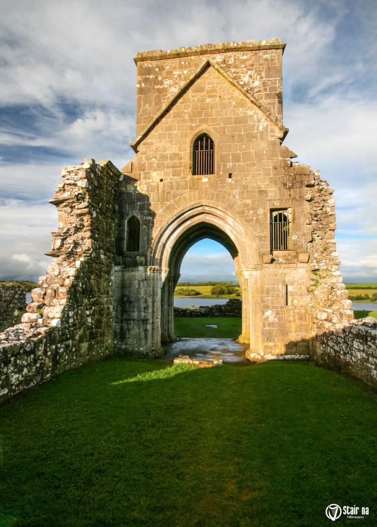 Ruins of Oratory of Saint Molaise abbey on Devenish Island with green lawn in foreground. Enniskillen, Northern Ireland