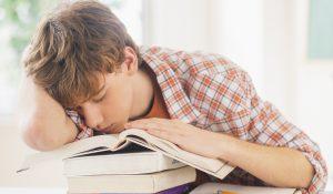 Teenage boy (14-15) sleeping in classroom