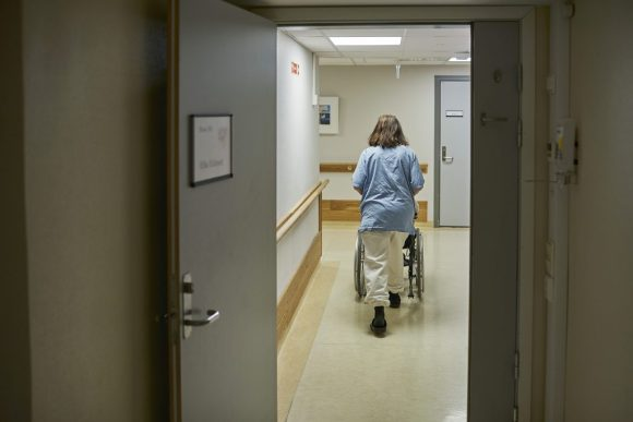 Illustrasjonsfoto av sykepleier som triller pasient på sykehjem