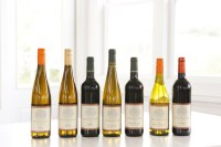 Photo of six wine bottles on a white table
