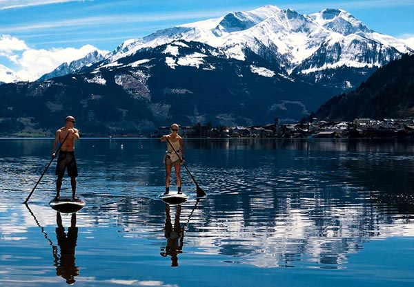 David Bengtsson standup paddling with mountains in back
