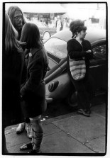 Group of young people talking on a sidewalk; to the side a woman leans against a VW Bug across from Pacific Drugs
