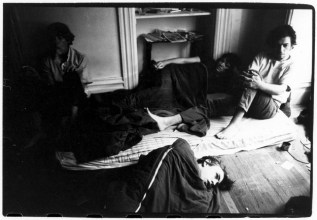 Hippies resting on mattress and on the floor