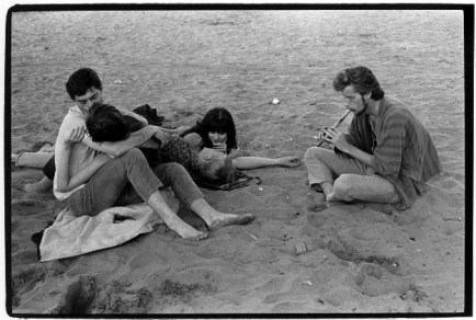 Two couples on a beach with a man to the right playing a wooden flute