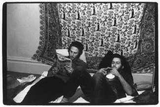 Two men in room with tapestry on wall; one reading Mad Magazine