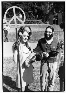 Woman with heavy makeup, a fur hat, and a mini skirt holding peace symbol next to smiling man with beard