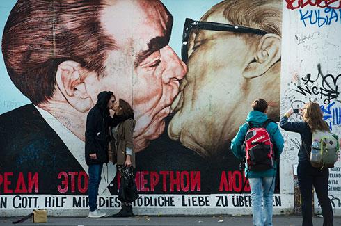 Туристи опонашају пољубац, овековечен на муралу, ондашњих лидера Совјетског Савеза и Источне Немачке, Леонида Брежњева и Ериха Хонекера (AFP Photo / John Macdougall)