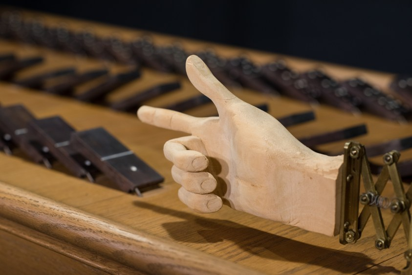 A wooden hand pushes down dominoes.