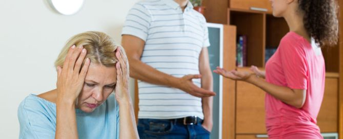 husband and wife quarrelling indoors, senior mother taking it hard