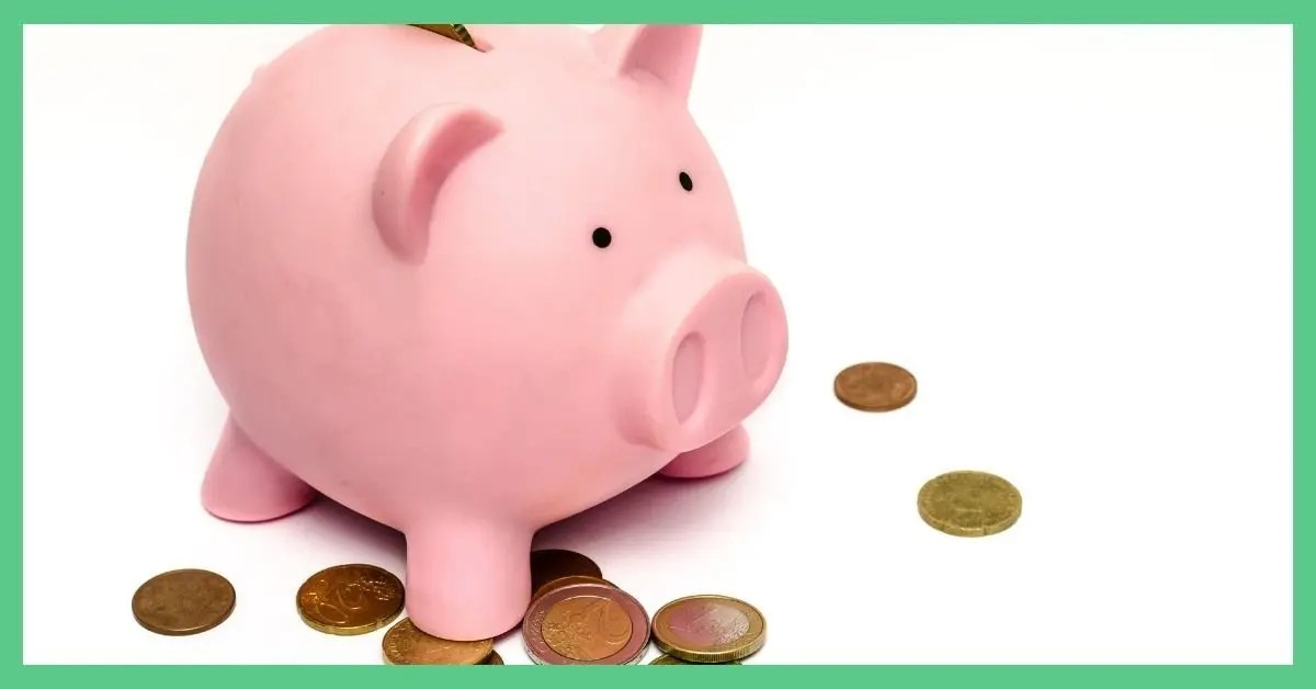 The image a pink piggy bank stood on a white surface with some coins at its feet.