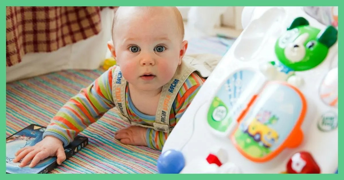 A baby crawling around. There's a baby walker to the right of the baby. Article is about travel cot hacks.