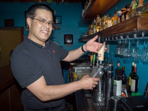 Javier Velesco pulls a draft beer at Cha Cha Cha's Fremont location. Having worked there seven years, he knows most of the neighborhood customers. (Judy Nelson)