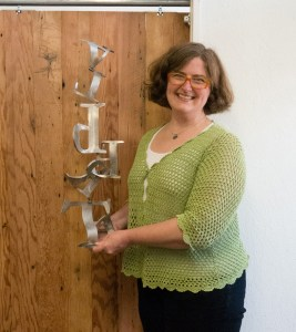 Alberta Main Street executive director Sarah Wittenberg holds a prototype of a metal sculpture designed by Ivan McLean. The finished sculpture will be eight feet tall and mounted on an eight-foot pedestal. The sculpture will be posted at the gateways to Alberta Arts District.