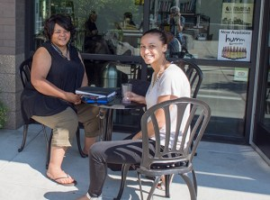 Rolanda E. Lively, left, a social work intern at Concordia University, and Rachel Gilmer, who works for the Portland African-American Leaders Forum, enjoy coffee at Elevated Coffee Shop in King. Customers play the piano inside the shop, where patrons join in by singing.