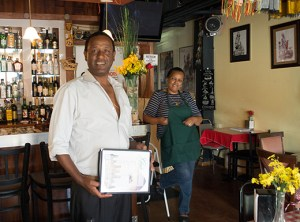 Gojos Restaurant owner Alex holds a menu of traditional Ethiopian fare. Mulu stands ready to serve diners who frequent the restaurant not only for its authentic cuisine, but also to see the traditional art and artifacts that decorate the walls.