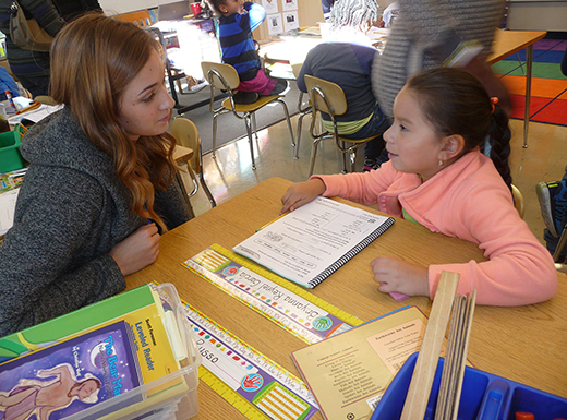 Brenna Huwe, left, a Concordia University practicum student, listens to second grader Bryanna Reynel Garcia, working on a science assignment. Faubion and Concordia are cooperating on a program to improve urban education. (Janet Goetze)