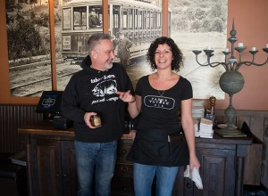 "Tabor Tavern owner Ken ""Zig"" Naffziger and waitress Rachel Slater share a laugh during a busy lunch-time service. A large vintage photo of a Tabor streetcar looms in the background while Zig holds a jar of their signature bacon jam. The Tavern is located on East Burnside in North Tabor."
