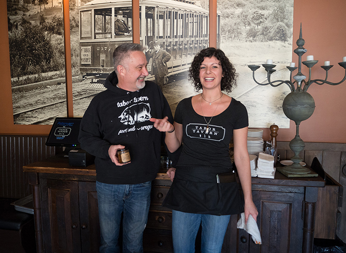 "Tabor Tavern owner Ken ""Zig"" Naffziger, left, and waitress Rachel Slater share a laugh during a busy lunch-time service. A large vintage photo of a Tabor streetcar looms in the background while Zig holds a jar of their signature bacon jam. The Tavern is located on East Burnside in North Tabor."