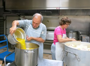 Nick Fkiaras transfers melted butter into a huge pot at the industrial kitchen located inside the church annex. Volunteers prepare to bake authentic Greek pastries and cookies for the annual Portland Greek Festival.