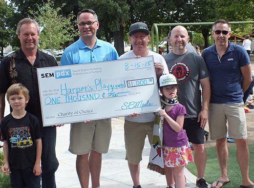 Search Engine Marketing Professionals of Portland board members, and their kids, present a check to Harpers Playground during the third annual Community Play Day. (SEMpdx)