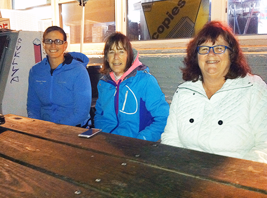 A group of Beaumont neighbors who call themselves 'Everest Watch' have rallied to support the Everest M Market family, who were robbed in September. In addition to fundraising efforts, the group recruits neighbors to gather at a picnic table outside of the market every evening from dusk until close. From left, Kim Warner, Susan Prows and Tracey Groupe work a shift on a recent Sunday evening. (Jane Perkins)