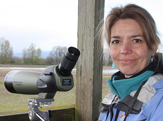 Dawn Nilson, creator of the Sauvie Island Recreation Guide, is shown here with a bird-spotting scope on Sauvie Island. (Dawn Nilson)