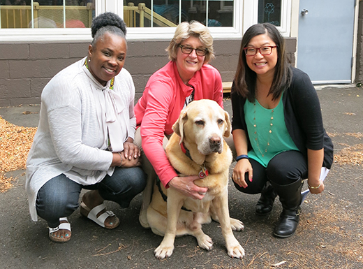Family Relief Nursery teacher Oletha Roberts, left, Lynn Parsons, and Family Relief Nursery program manager Crystal Ross, take a break with Parson's therapy assistance dog, Manny. Children who attend therapeutic classes and playground time, enjoy visits with Manny who brings them comfort and joy. (Kathy Eaton)