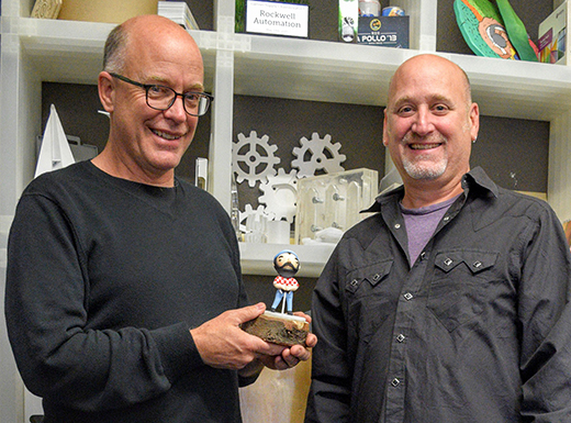 Standing in front of their library of projects, Figure Plant's company owner/founder David Frederickson and company director John Ceniceros hold a limited-edition handcrafted Paul Bunyan doll made by the Bamboo Craftsman to support fund-raising to restore the iconic statue in Kenton. (John Butenschoen)